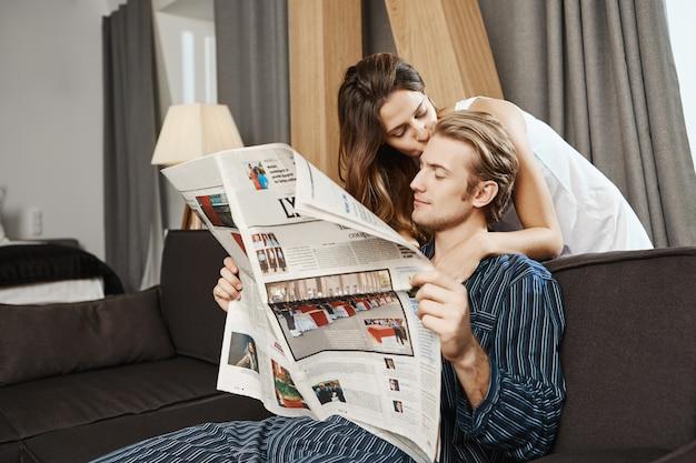 Przystojna Para Czyta Gazetę W Salonie Przed śniadaniem. Przystojny Facet Sprawdza Wiadomości, Gdy Jego Dziewczyna Mówi, że śniadanie Jest Gotowe I Czule Całuje Faceta W Czoło. Darmowe Zdjęcia