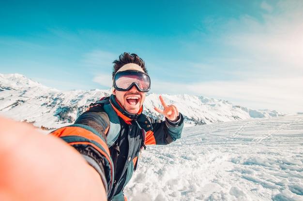 Przystojna śmieszna Narciarka Bierze Selfie W Zimie W śniegu Na Górze Premium Zdjęcia