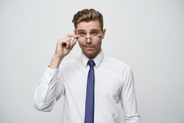 Przystojny, Atrakcyjny Młody Człowiek Z Stylową Fryzurą Koryguje Okulary Darmowe Zdjęcia