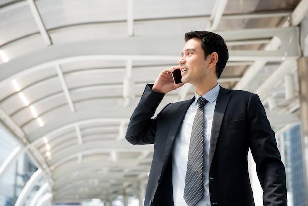 Przystojny Azjatycki Biznesmen Dzwoni Na Smartphone Podczas Gdy Chodzący W Mieście Premium Zdjęcia
