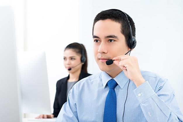 Przystojny azjatycki męski telemarketingowy obsługa klienta agent pracuje w centrum telefonicznym Premium Zdjęcia