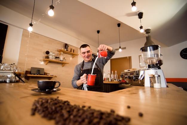 Przystojny barista przygotowywa filiżankę kawy dla klienta w sklep z kawą. Premium Zdjęcia