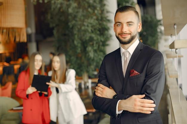 Przystojny biznesmen z kobietami stoi i pracuje w kawiarni Darmowe Zdjęcia