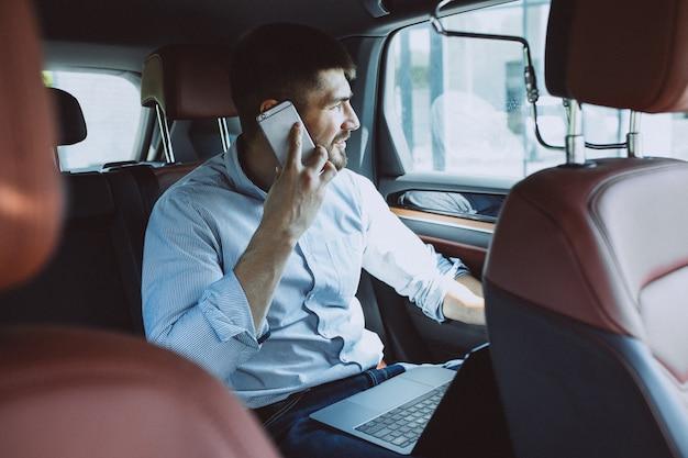 Przystojny biznesowy mężczyzna pracuje na komputerze w samochodzie Darmowe Zdjęcia