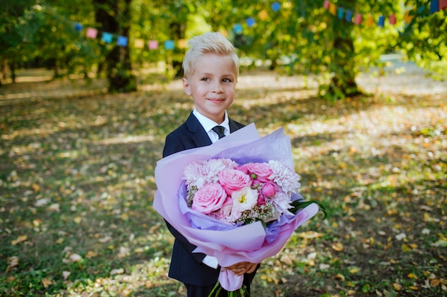 Przystojny Blond Uczeń W Mundurek Szkolny Trzyma Bukiet Premium Zdjęcia
