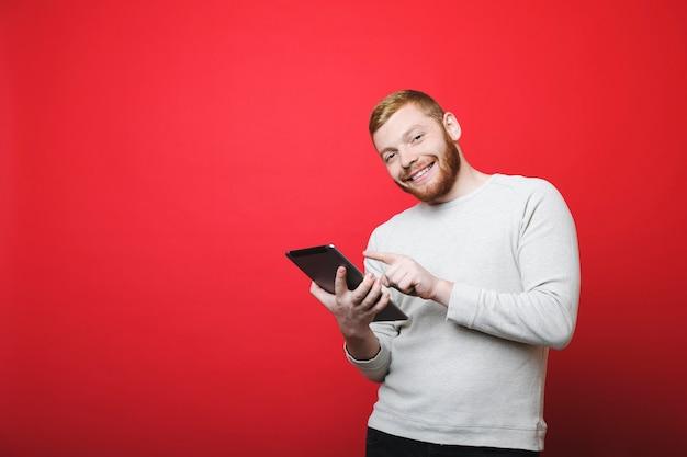 Przystojny Brodaty Facet Uśmiechając Się I Patrząc Na Kamery, Stojąc Na żywym Czerwonym Tle I Za Pomocą Tabletu Premium Zdjęcia
