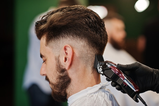 Przystojny brodaty mężczyzna w zakładzie fryzjerskim, fryzjer w pracy. bliska kark. Premium Zdjęcia