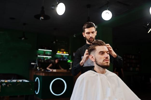 Przystojny Brodaty Mężczyzna W Zakładzie Fryzjerskim, Fryzjer W Pracy. Premium Zdjęcia