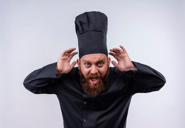 Przystojny Brodaty Szef Kuchni W Czarnym Mundurze Trzymając Się Za Ręce Na Uszach, Próbując Usłyszeć Coś Na Białej ścianie Darmowe Zdjęcia
