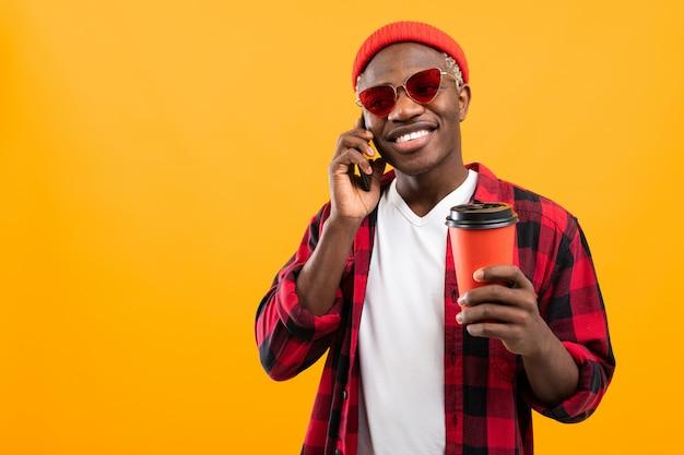 Przystojny Czarnego Amerykanina Mężczyzna Opowiada Na Telefonie Podczas Gdy Trzymający Oddalonego Kawowego Szkło Na żółtym Pracownianym Tle Premium Zdjęcia