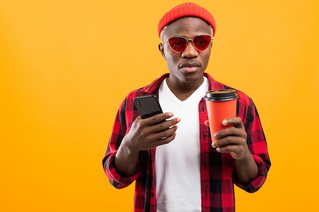 Przystojny Czarnego Amerykanina Mężczyzna Z Telefonem I Szkłem Takeaway Kawa Na żółtym Pracownianym Tle Premium Zdjęcia