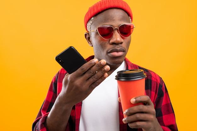 Przystojny Czarny Amerykański Mężczyzna Z Telefonem I Szkłem Wynos Kawy Na żółty Premium Zdjęcia