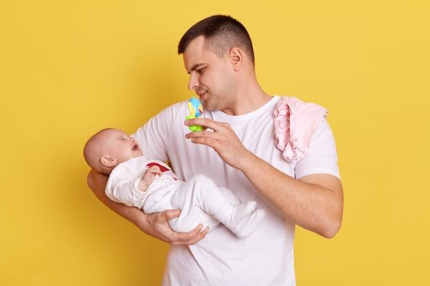 Przystojny Europejczyk Ubrany W Zwykłą Białą Koszulkę Stoi Na żółtej ścianie Ze Swoim Nowonarodzonym Dzieckiem, Patrząc Na Swoją Malutką Córeczkę, Trzymając Worek Fasoli I Pokazując Dzieciakowi, Próbując Uspokoić Dziecko. Premium Zdjęcia