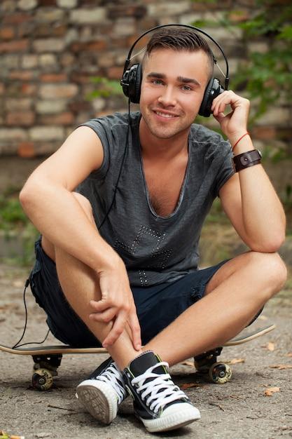 Przystojny facet siedzi na ulicy Darmowe Zdjęcia