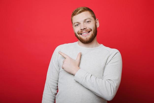 Przystojny Facet Z Rudą Brodą, Uśmiechając Się I Patrząc Na Kamery, Stojąc Na Jasnym Czerwonym Tle I Wskazując Palcem Wskazującym Premium Zdjęcia