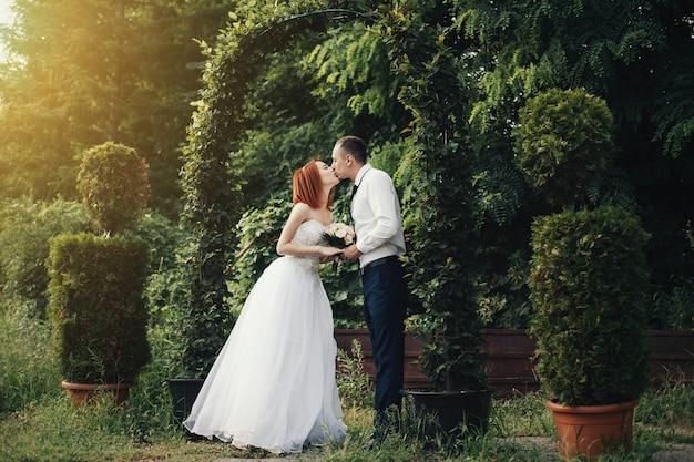 Przystojny Fornal Trzyma Panny Młodej Rękę Blisko Zielonego Kwiatu Archway Premium Zdjęcia