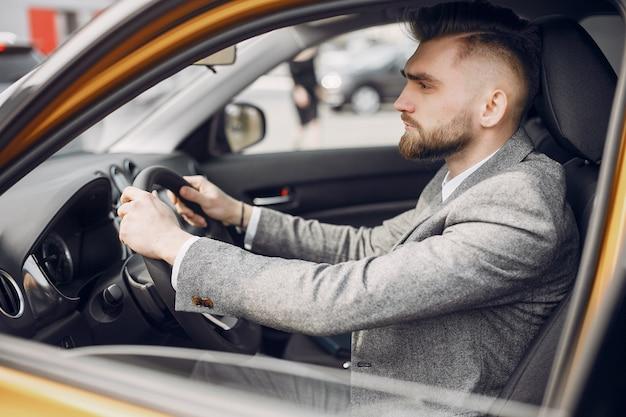 Przystojny i elegancki mężczyzna w samochodowym salonie Darmowe Zdjęcia