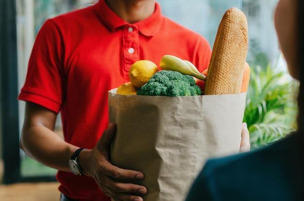 Przystojny Karmowy Doręczeniowej Usługa Mężczyzna W Czerwonej Koszulowej Mienia świeżej żywności Ustalonej Torbie Klient Przy Drzwi Domem, Ekspresowa Dostawa Premium Zdjęcia