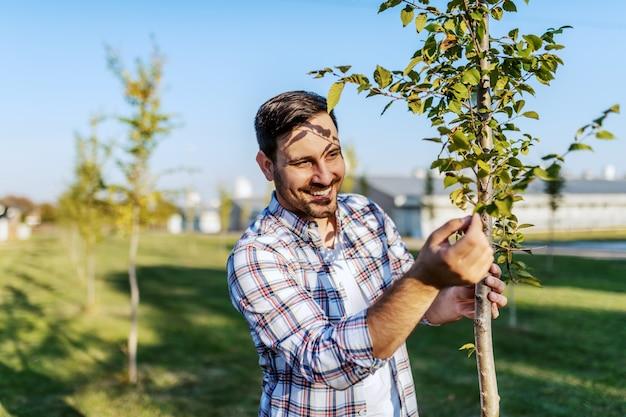Przystojny Kaukaski Uśmiechnięty Rolnik Stojący W Sadzie I Sprawdzanie Na Drzewie Owocowym. Premium Zdjęcia