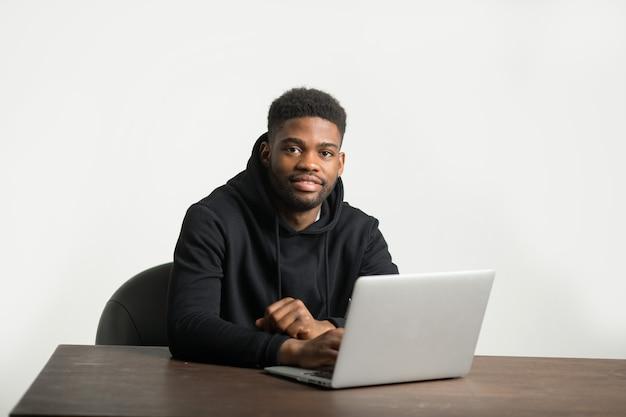 Przystojny Mężczyzna Afryki W Dresie Siedzi Przy Stole Z Laptopem Premium Zdjęcia