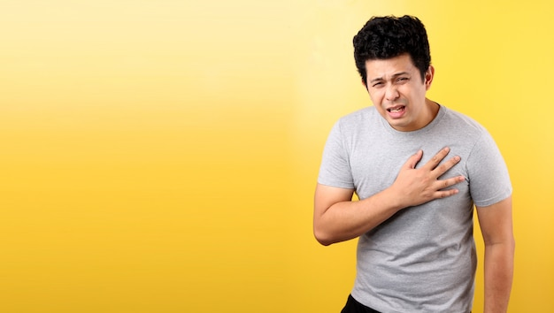 Przystojny Mężczyzna Azji Z Bólem Serca, Na żółtej ścianie. Premium Zdjęcia
