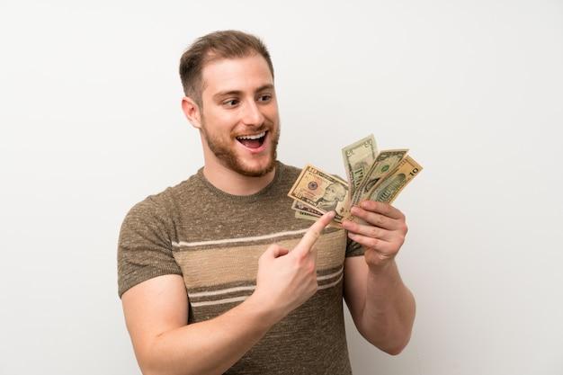 Przystojny Mężczyzna Nad Odosobnioną Biel ścianą Bierze Mnóstwo Pieniądze Premium Zdjęcia
