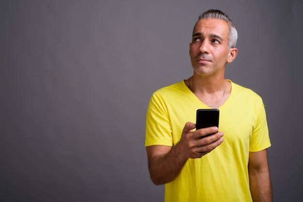 Przystojny Mężczyzna Perski Z Siwymi Włosami Na Sobie żółtą Koszulkę Premium Zdjęcia