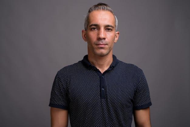 Przystojny Mężczyzna Perski Z Siwymi Włosami Na Szarym Tle Premium Zdjęcia