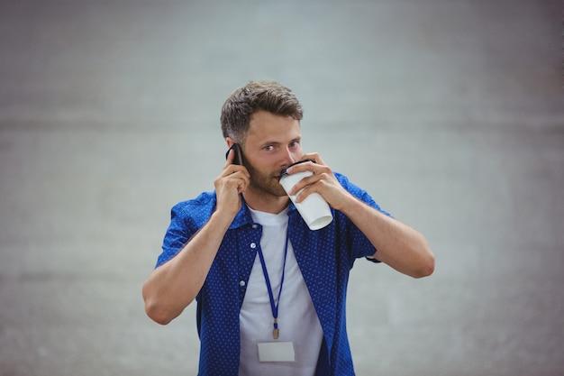 Przystojny Mężczyzna Pije Kawę Podczas Gdy Opowiadający Na Telefonie Komórkowym Premium Zdjęcia