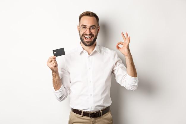 Przystojny Mężczyzna Pokazując Swoją Kartę Kredytową I Znak W Porządku, Polecając Bank, Stojąc Miejsce Darmowe Zdjęcia