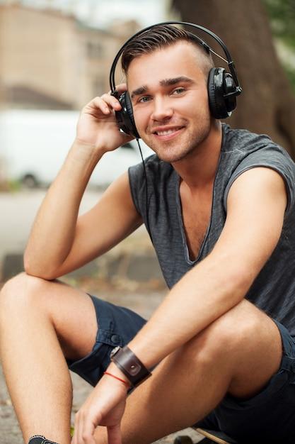 Przystojny Mężczyzna Siedzi Na Ulicy Ze Słuchawkami Darmowe Zdjęcia