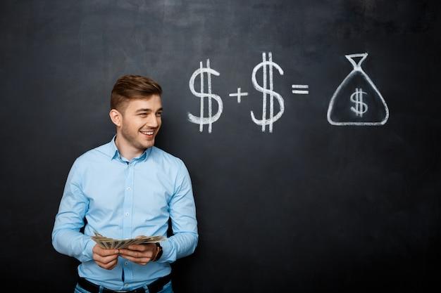 Przystojny Mężczyzna Stoi Nad Blackboard Z Patroszonym Dolarowym Pojęciem Darmowe Zdjęcia