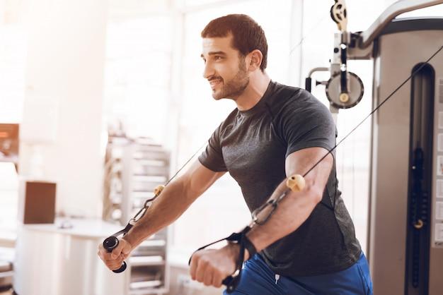 Przystojny mężczyzna trenuje na siłowni. Premium Zdjęcia