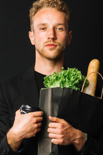 Przystojny mężczyzna trzyma torbę na zakupy spożywcze Darmowe Zdjęcia