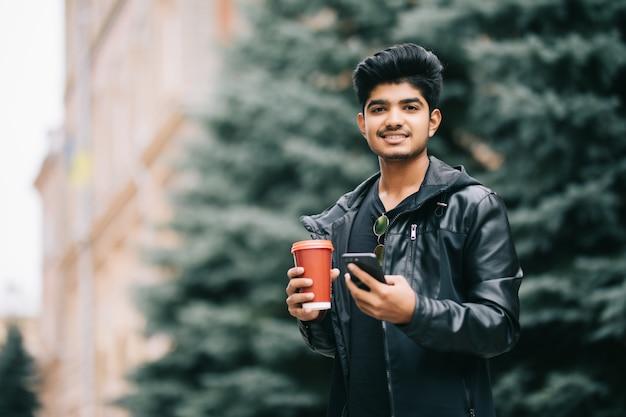 Przystojny Mężczyzna Uczeń Opowiada Z Przyjaciółmi Na Telefonie Komórkowym Cieszy Się Miastową Kawę Z Eyeglasses Podczas Gdy Chodzący Na Ulicie Darmowe Zdjęcia