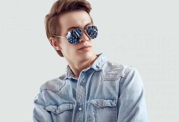 Przystojny mężczyzna w modne okulary przeciwsłoneczne na sobie kurtkę jeansy Premium Zdjęcia