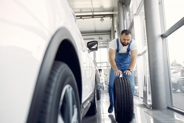 Przystojny Mężczyzna W Niebieskim Mundurze Sprawdza Samochód Darmowe Zdjęcia