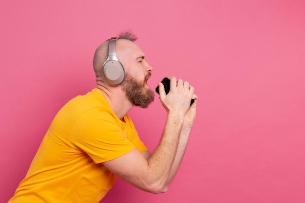 Przystojny Mężczyzna W Swobodnym śpiewie Ze Słuchawkami Do Telefonów Komórkowych Na Białym Tle Na Różowym Tle Darmowe Zdjęcia