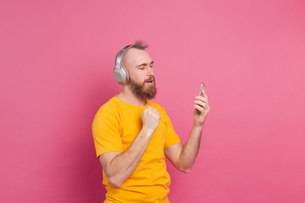 Przystojny Mężczyzna W Swobodnym Tańcu Z Telefonem Komórkowym I Słuchawkami Na Białym Tle Na Różowym Tle Darmowe Zdjęcia