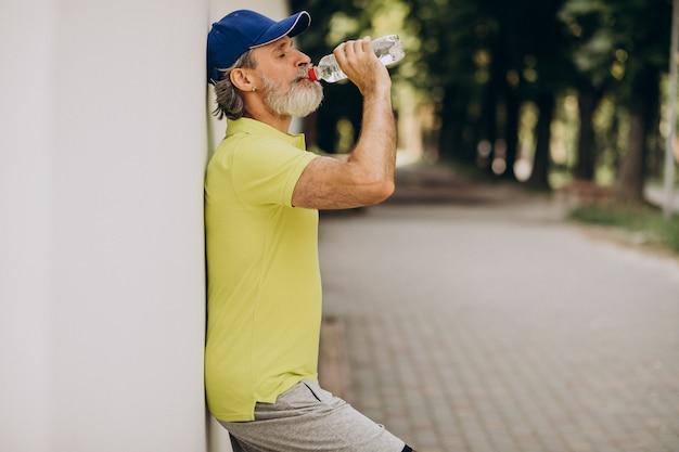 Przystojny Mężczyzna Wody Pitnej W Parku Po Joggingu Darmowe Zdjęcia
