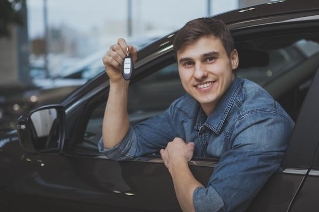Przystojny mężczyzna wybiera nowego samochód kupować Premium Zdjęcia