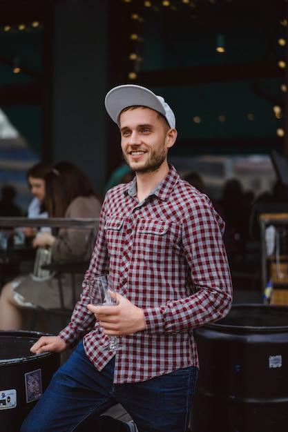 Przystojny Mężczyzna Wytatuowany Na Tarasie Letnim W Kawiarni W Mieście Pije Wino. Street Cafe. Darmowe Zdjęcia
