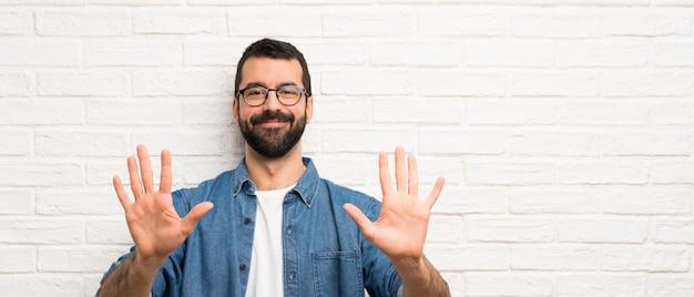 Przystojny Mężczyzna Z Brodą Na Białym Murem Licząc Dziesięć Palcami Premium Zdjęcia
