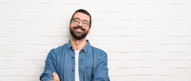 Przystojny Mężczyzna Z Brodą Nad Białym Murem Z Okularami I Szczęśliwy Premium Zdjęcia