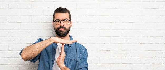 Przystojny mężczyzna z brodą nad białym ściana z cegieł robi czasowi out gestykuluje Premium Zdjęcia