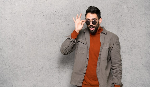Przystojny mężczyzna z brodą z szkłami i zaskakujący nad textured ścianą Premium Zdjęcia