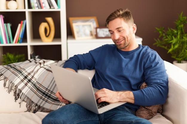 Przystojny Mężczyzna Z Współczesnym Laptopem W Domu Darmowe Zdjęcia