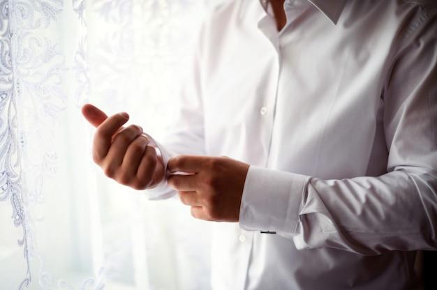 Przystojny mężczyzna zapina białą koszulę stojący przy oknie rano na ślub. Premium Zdjęcia