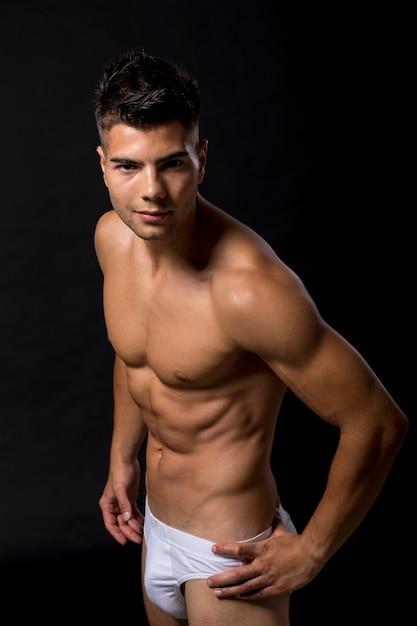 Przystojny mięśniowy młody człowiek pozuje w studiu Premium Zdjęcia