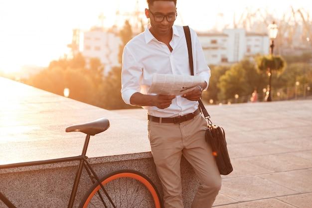 Przystojny Młody Afrykański Mężczyzna W Wczesnym Poranku Z Rowerową Czytelniczą Gazetą. Darmowe Zdjęcia
